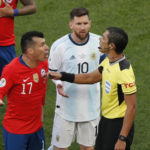 Chile's Gary Medel, left, and Argentina's Lionel Messi, center, protest to referee Mario Diaz